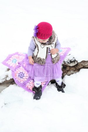 Photo for Little girl sitting outside in the snow - Royalty Free Image