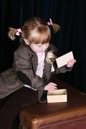 Photo for Little girl in vintage attire playing with a puzzle - Royalty Free Image