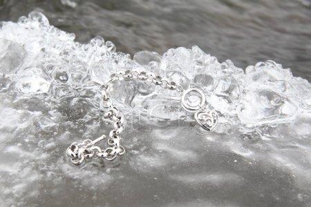 Photo pour Couche de glace avec un charme bracelet en forme de coeur - image libre de droit