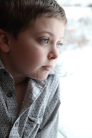 Photo pour Jeune garçon regardant par la fenêtre un jour d'hiver - image libre de droit