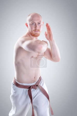 Karate man in a kimono demonstrate pose