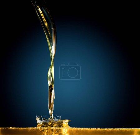Zbliżenie: olej i płyn wylewanie na ciemnym tle.