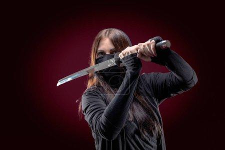 Beautiful samurai woman warrior with a sword in studio