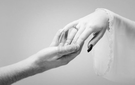 Hände von Mann und Frau, die auf grauem Hintergrund zueinander greifen. Schwarz-Weiß-Foto