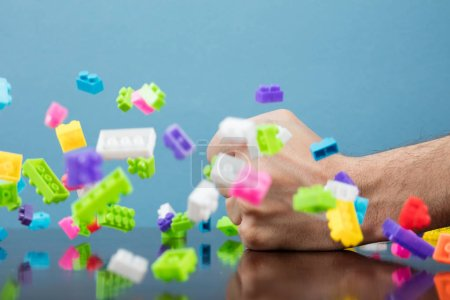Pile of colored toy bricks falling on dark background.