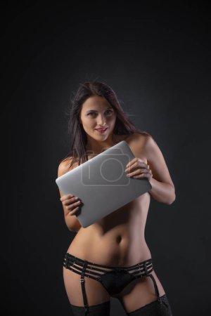 Photo pour Gros plan de Sexy jeune femme brune en lingerie sensuelle noire à l'aide d'un ordinateur portable et posant sur un mur de fond noir en studio . - image libre de droit
