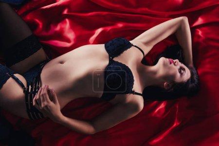 Photo pour Sexy jeune femme brune en lingerie sensuelle noir et bas posant sur le lit en studio. - image libre de droit