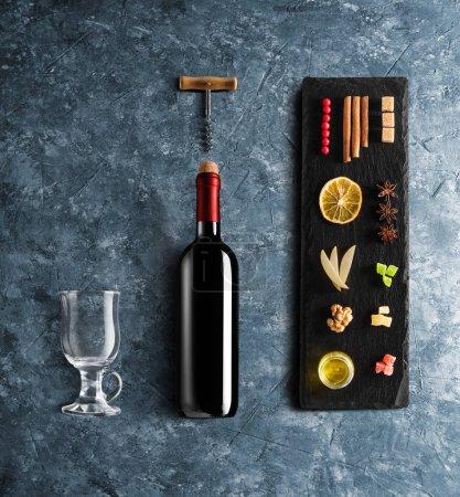 Photo pour Recette de vin chaud ingrédients et accessoires de cuisine, bouteille de vin rouge, cannelle, étoiles d'anis, orange, sucre brun et épice sur fond de pierre bleue . - image libre de droit