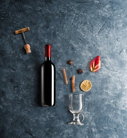 Photo for Mulled wine recipe ingredients and kitchen accessories, bottle of red wine, cinnamon, anise stars, orange, brown sugarand spice on blue stone background. - Royalty Free Image