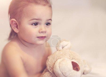 Photo pour Portrait d'un petit garçon mignon avec un jouet ours doux à la maison, réveillé après un rêve avec son meilleur ami, heureux childhoo insouciant - image libre de droit