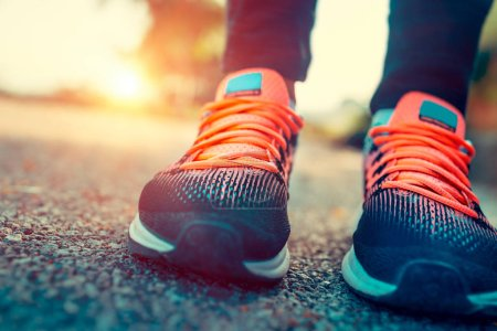 Running in the sunny summer day, closeup photo of a women's sportive shoes, body part, female feet, training outdoors, healthy sportive lifestyl