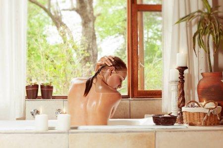 Photo pour Dos d'une femme dans la baignoire lave ses cheveux, dorloter dans le spa de luxe hôtel, hygiène et plaisir concep - image libre de droit