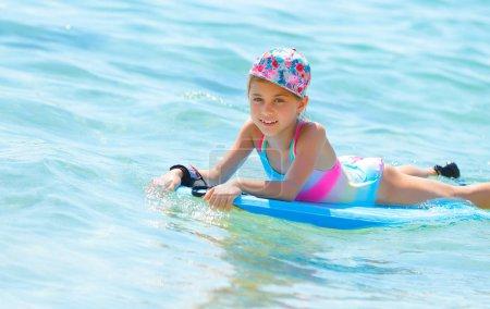 Happy little girl with bodyboard in blue transparent sea, enjoying water sport, having fun in summer cam