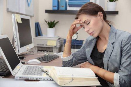 Mujer cansada en el trabajo, hermosa mujer de negocios en la oficina sufre de dolor de cabeza, problemas con los documentos, concepto de trabajo duro de la oficina