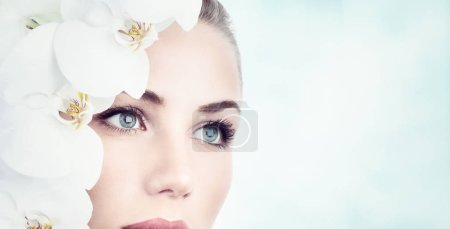 Photo for Closeup portrait of a beautiful young woman with white orchids near face over clean background, natural facial cosmetics, day at spa, beauty and health concep - Royalty Free Image