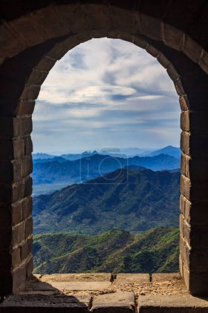 View onto a mountain range through a window in one of the watchtowers of the Great Wall of China, in the Mutianyu village, near Beijing