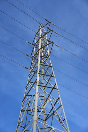 Electric tower view from below under blue sky