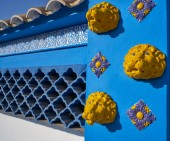 Mediterranean facade in blue with yellow lion tiles and ceramic lattice