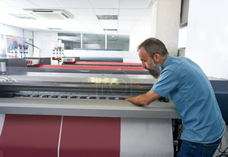 Espertise man in transfer printing industry plotter printer hipster beard