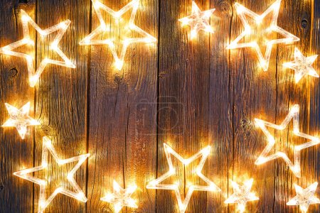 Christmas glowing stars on vintage wooden background copy space