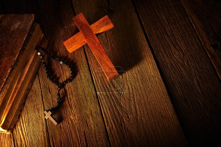 Christian cross on wood bible and rosary beads over wooden vintage background