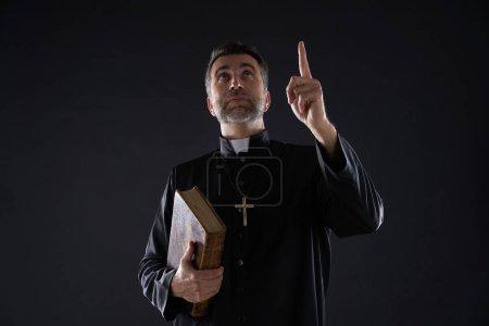 Photo pour Mâle de prêtre tenant le doigt pointé bible au ciel dans le ciel - image libre de droit