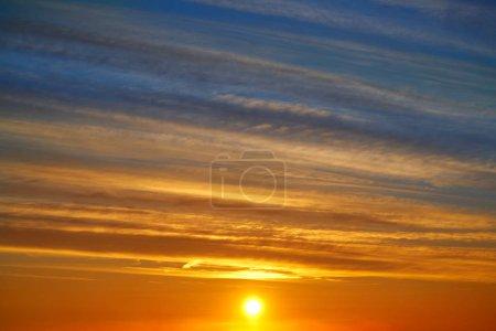 Ciel de nuages du coucher du soleil sur fond orange et bleu