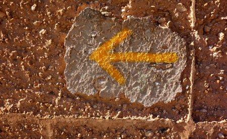 Photo pour Signe de la flèche jaune de façon Camino de Santiago des pèlerins de Saint Jacques en mur d'adobe - image libre de droit