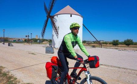 Photo pour Pèlerin motard par Camino de Santiago en vélo au moulin à vent de Castille La Manche - image libre de droit