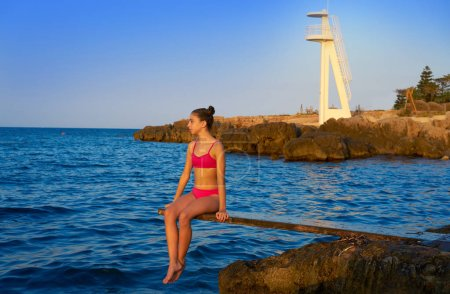 Foto de Chica en la playa puesta de sol en trampolín trampolín - Imagen libre de derechos