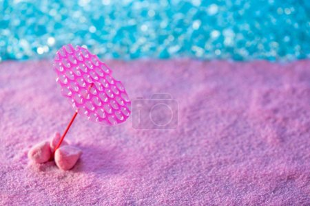 Photo for Beach vacation concept pink sand parasol and mat and turquoise sea water - Royalty Free Image