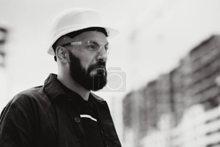 Photo for Nervous, evil man in a helmet and in work clothes - Royalty Free Image