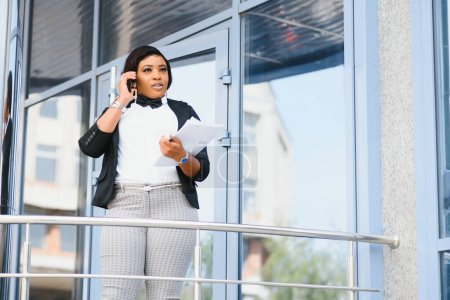 Photo for Half length portrait of confident successful african american female employee in white shirt holding smartphone and folder with documents in hands while smiling at camera standing near office building - Royalty Free Image