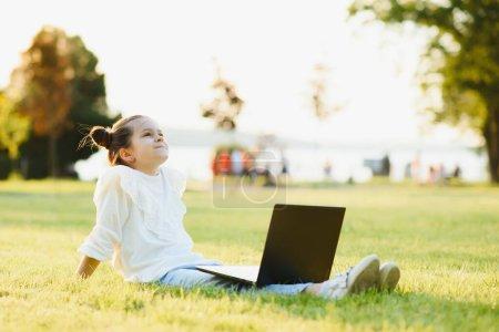 Photo pour Petite fille assise dans le parc et travaillant avec un ordinateur portable. Éducation, mode de vie, concept technologique - image libre de droit