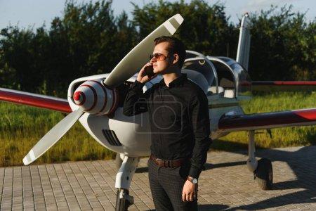 Foto de Joven hombre de negocios guapo está de pie cerca de avión privado. Hombre seguro y exitoso en el aeropuerto. - Imagen libre de derechos
