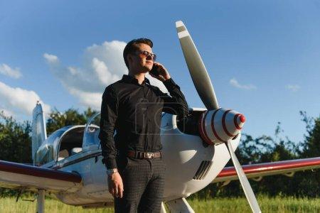 Photo pour Bel homme d'affaires près d'un jet privé. Un homme qui réussit à l'aéroport parle au téléphone. - image libre de droit