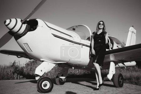 Photo pour Pleine longueur de femme riche en robe élégante debout contre la limousine et privé - image libre de droit