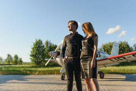 Photo for Beautiful young stylish couple in official clothes is standing near private plane. - Royalty Free Image