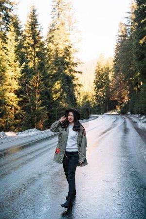 Photo pour Fille heureuse avec chapeau dans la forêt à fond de route de montagne, Détendez-vous sur le voyage concept de vacances, couleur de ton vintage et mise au point douce - image libre de droit