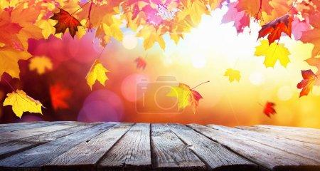 Photo pour Automne fond coloré avec des feuilles et une table en bois à la lumière du soleil - image libre de droit