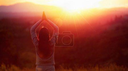 Photo pour Femme de yoga méditant au coucher du soleil. Modèle féminin méditant en harmonie sereine - image libre de droit