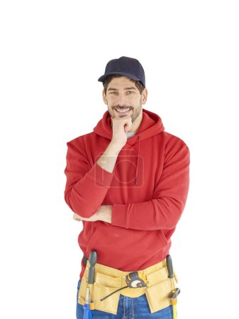 Happy young handyman wearing baseball cap and hoodie while standing at isolated white background wiht hand on his chin.