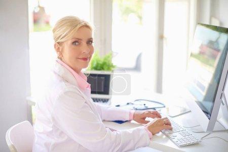 Smiling senior female doctor working in light office