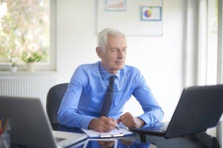 Photo pour Handsome senior businessman doing some paperwork sitting at office desk and working on presentation. - image libre de droit