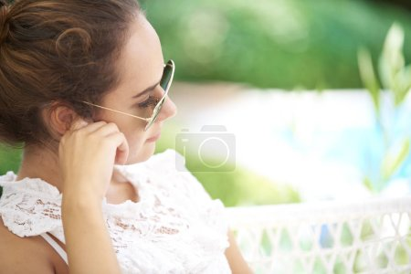 portrait of beautiful young woman sitting outdoor and relaxing in garden
