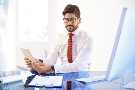 Photo pour Portrait shot of handsome young businessman wearing shirt and tie while sitting at office desk and holding hand digital tablet. - image libre de droit