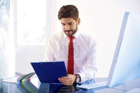 Photo pour Prise de vue de vendeur assistant professionnel tenant presse-papiers dans sa main alors qu'il était assis au bureau et faisant de la paperasse . - image libre de droit