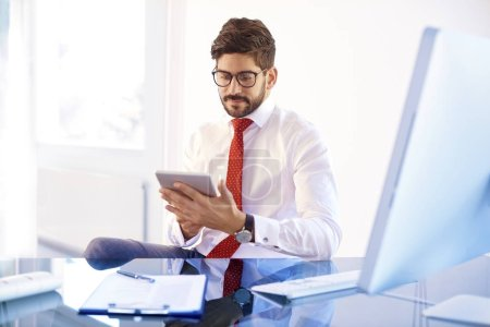 Photo pour Shot of young businessman using digital tablet while sitting at office and working on new project. - image libre de droit