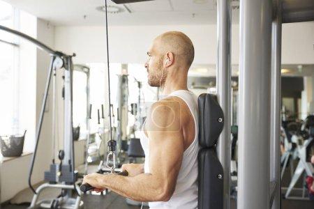 Photo pour Shot of sporty man doing exercises in gym. - image libre de droit
