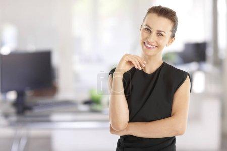 Photo pour Portrait d'une jeune femme d'affaires exécutif permanent au bureau tout en souriant et en regardant la caméra. - image libre de droit